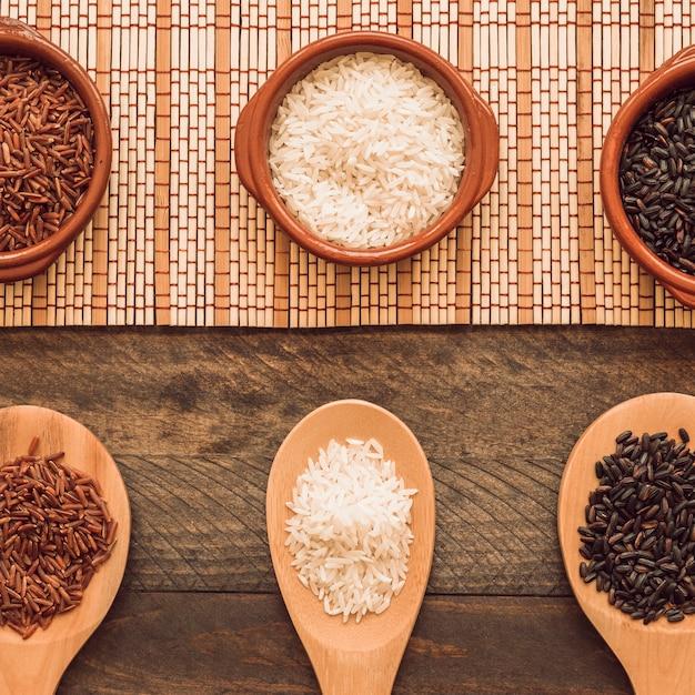 Colher de pau e tigela de grãos de arroz na mesa de madeira Foto gratuita