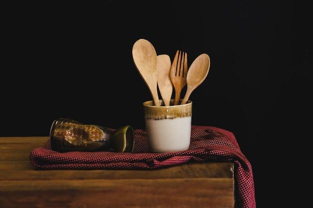 Colher e forquilha de madeira no copo, ainda conceito da vida. Foto Premium