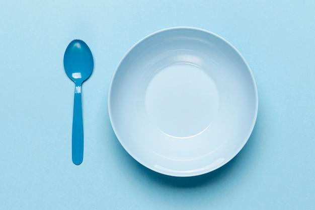 Colher e tigela azul vazia de vista superior Foto gratuita