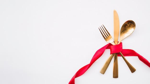 Colher, faca e garfo com fita vermelha Foto gratuita