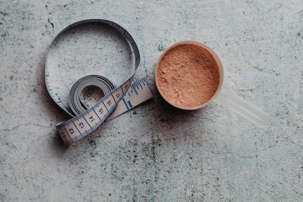 Colher ou colher de proteína de soro de leite com textura visível. sabor de chocolate. fundo de concreto Foto Premium