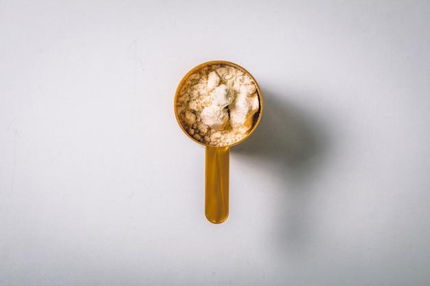 Colheres cheias de pó de baunilha de proteína. vista do topo Foto Premium
