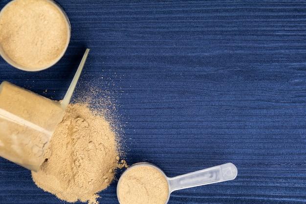 Colheres cheias de pó de proteína na madeira azul de fundo Foto Premium