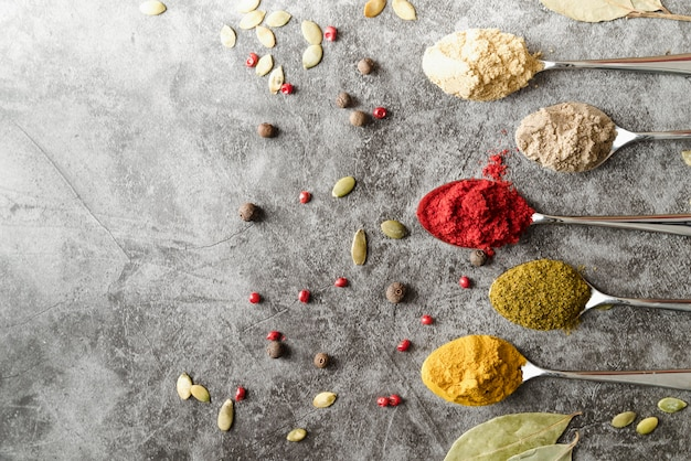 Colheres com vários pós e sementes de condimentos Foto gratuita