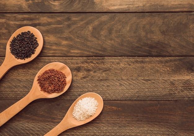 Colheres de madeira com três diferentes tipos de grãos de arroz na prancha de madeira Foto gratuita