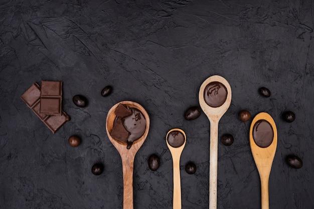 Colheres de pau com calda de chocolate e barras de chocolate Foto gratuita