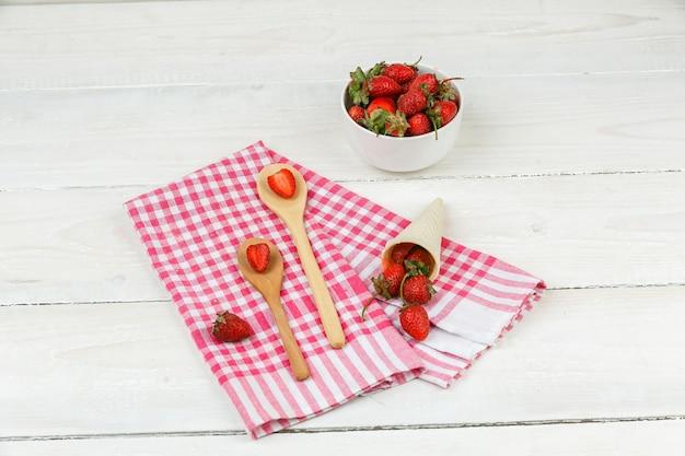 Colheres de pau de close-up e um cone de morangos na toalha de mesa de algodão vermelho com uma tigela de morangos na superfície da placa de madeira branca. horizontal Foto gratuita