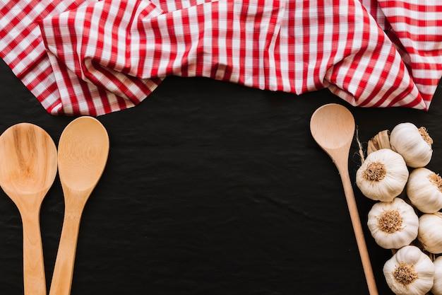 Colheres e alho fresco perto de guardanapo Foto gratuita