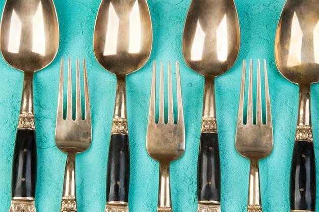 Colheres e garfos de bronze no fundo concreto. Foto Premium
