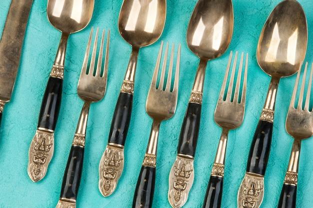 Colheres, garfos e facas de latão sobre fundo de concreto. Foto Premium