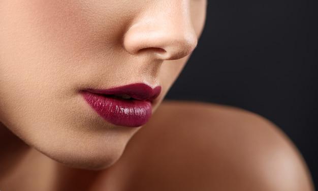 Colhido perto acima dos bordos da mulher cobertos com o batom escuro. Foto Premium