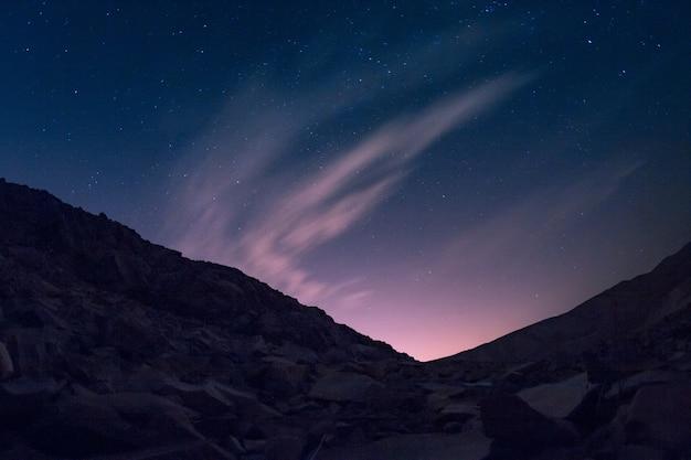 Colina com muitas peças de metal sob o lindo céu estrelado com aurora Foto gratuita