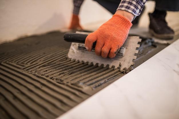 Colocação de telhas cerâmicas. colocar argamassa em um piso de concreto como preparação para o assentamento de ladrilhos brancos. Foto gratuita