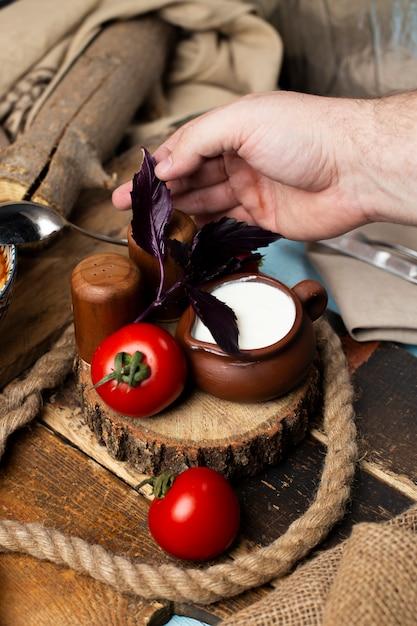 Colocando tomates, iogurte e folhas de vermelho basílico juntos. Foto gratuita