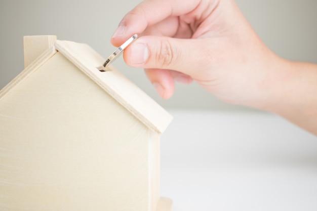 Colocar dinheiro em uma caixa modelo de uma casa de madeira Foto Premium