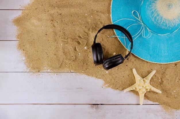 Coloque acessórios de praia para férias planas com fones de ouvido de chinelos de praia e chapéu de praia no verão Foto Premium
