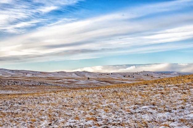 Coloque com árvores e céu com nuvens na sibéria, ilha olkhon no inverno Foto Premium