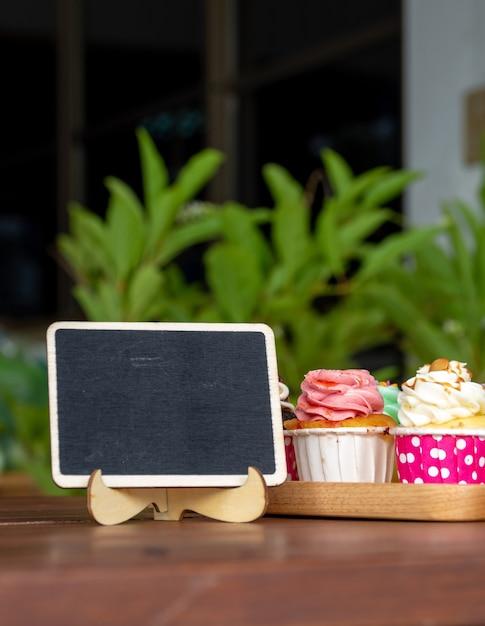 Colorido, de, caseiro, cupcake, ligado, madeira, bandeja, com, vazio, quadro-negro, e, espaço cópia, para, seu Foto Premium