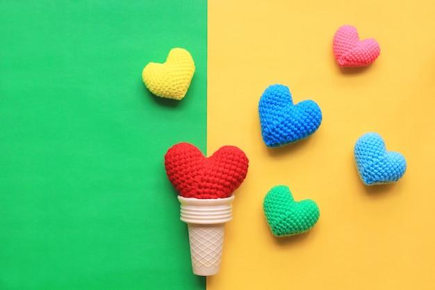 Colorido do coração handmade do crochet no copo do waffle no fundo amarelo e verde para o dia dos valentim Foto Premium