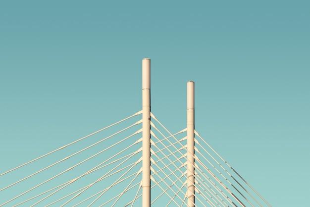Colunas e cabos brancos de uma ponte com o céu azul ao fundo Foto gratuita