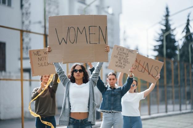 Com as mãos levantadas. grupo de mulheres feministas protesta por seus direitos ao ar livre Foto gratuita