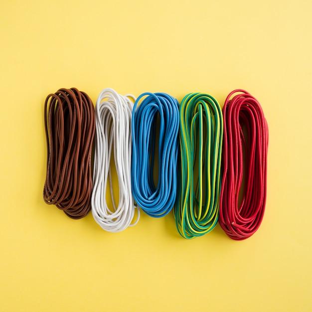 Com fios coloridos dispostos em uma fileira no pano de fundo amarelo Foto gratuita