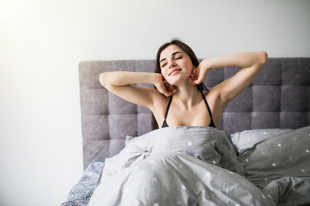 Começando novo dia. mulher jovem e bonita em lingerie, mantendo as mãos no cabelo enquanto está sentado na cama Foto gratuita
