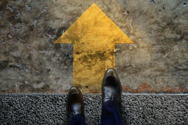 Comece e desafie o conceito. um homem de negócios com sapatos formais passos para seguir uma seta amarela, prepare-se para seguir em frente ou dê uma chance ao sucesso. vista do topo Foto Premium
