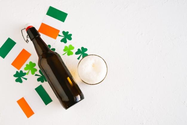 Comemoração do dia de são patrício. cerveja decorada com bandeiras irlandesas e trevos. copie o espaço. vista do topo. Foto Premium