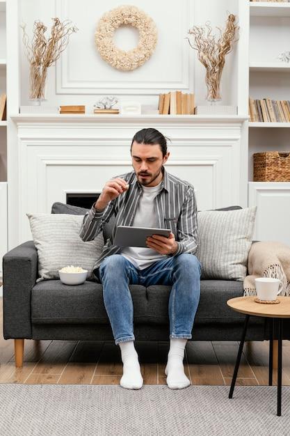 Comendo pipoca e usando dispositivo digital de longo alcance Foto Premium