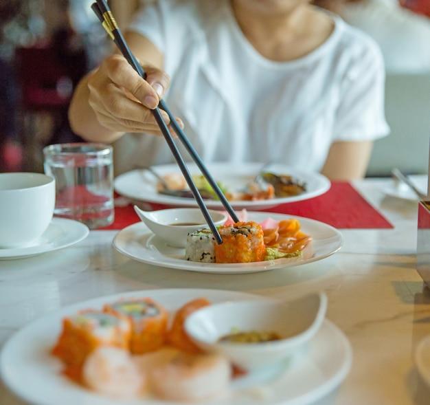 Comendo shushi com pauzinhos, foco seletivo Foto Premium