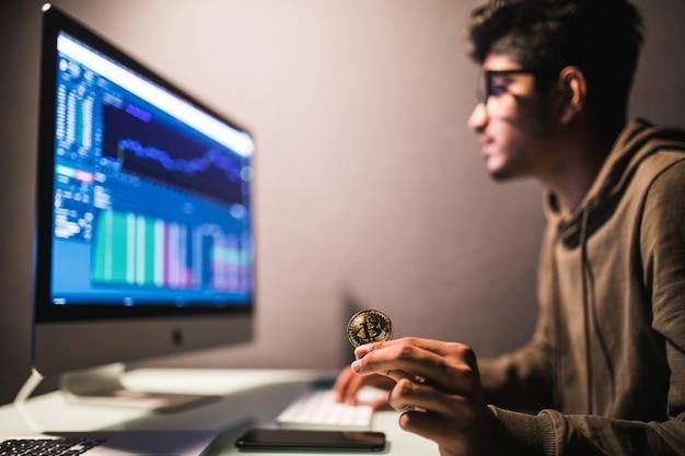 Comerciante de bitcoin indiano, verificando o conceito de análise de dados de negociação de ações, trabalhando no escritório com gráfico financeiro em monitores de computador Foto gratuita