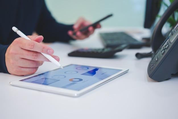Comerciante homem mão no tablet com painel de estoque gráfico e segurando o smartphone para verificar notícias na mesa Foto Premium