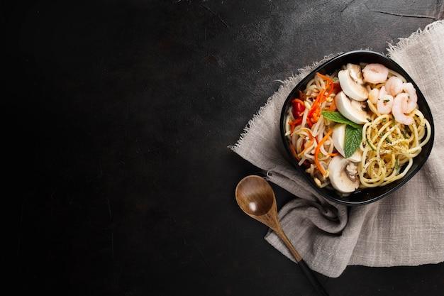 Comida asiática deliciosa e saudável em um plano de fundo texturizado preto com espaço de cópia Foto gratuita