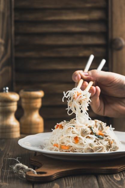 Comida asiática macarrão funchoza com frango e varas para comida na madeira com copyspace Foto Premium