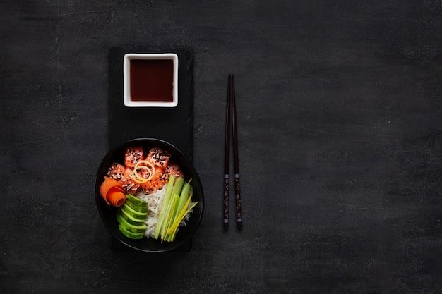 Comida asiática na moda, tigela de sushi poke com pepino, salmão, cenoura, abacate, sementes de gergelim Foto Premium