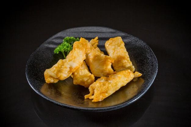 Comida asiática, tofu de peixe frito no fundo preto, comida tradicional japonesa Foto Premium