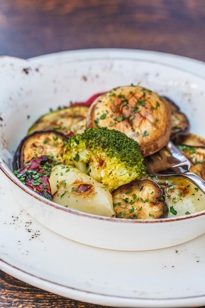 Comida balcânica nacional grelhado legumes em um prato branco em cima da mesa no restaurante Foto Premium