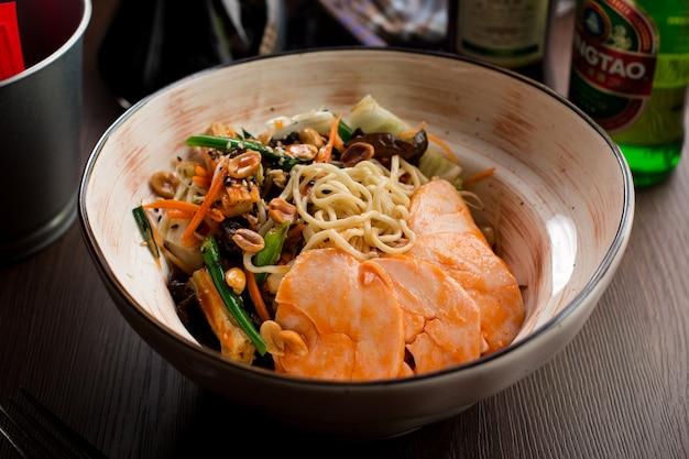 Comida chinesa: frango com macarrão e amendoim Foto Premium