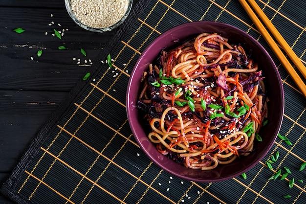 Comida chinesa. macarrão frito de vegan com couve roxa e cenoura em uma tigela sobre um fundo preto de madeira. Foto Premium