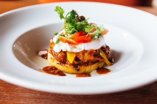 Comida de fusão: cobertura de canapé de hambúrguer com ovo, tomate e coentro. Foto Premium