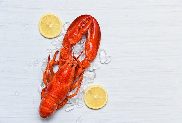 Comida de lagosta no camarão de frutos do mar de gelo com limão no jantar de mesa de madeira branca Foto Premium