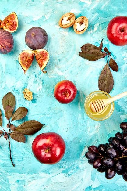 Comida de outono ainda vida com estação frutas uva, maçãs vermelhas e figos em uma mesa azul. Foto Premium