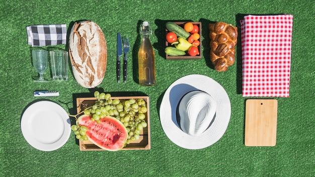 Comida de piquenique; pão; frutas; placa; tábua de cortar; toalha de mesa no relvado verde Foto gratuita