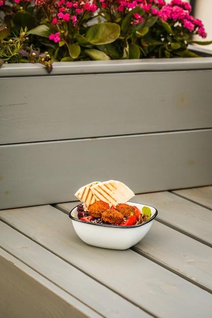Comida de rua israelense. salada do falafel com hummus, beterraba e vegetais na bacia em um restaurante. Foto Premium