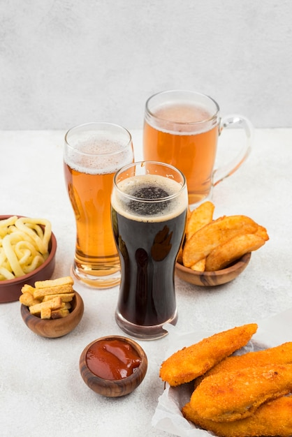 Comida deliciosa e copos de cerveja Foto gratuita
