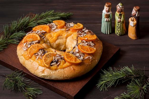 Comida do dia da epifania com laranjas fatiadas e personagens sagrados em miniatura Foto gratuita