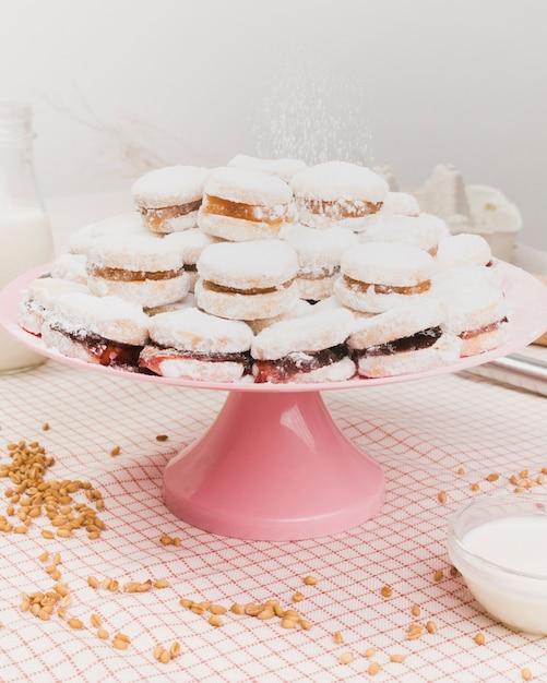 Comida doce polvilhado com açúcar em pó no suporte do bolo com grão de trigo e tigela de leite sobre tecido xadrez Foto gratuita