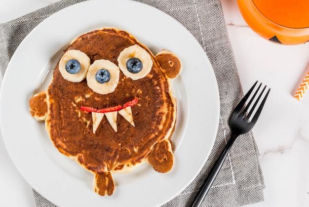 Comida engraçada para o halloween. panqueca de café da manhã para crianças decorada como monstro assustador, com banana, frutas, suco de abóbora batido, mesa branca Foto Premium