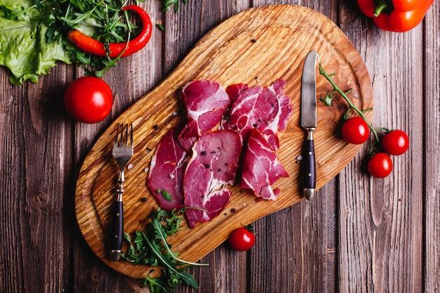 Comida fresca e saudável. carne vermelha fatiada situa-se na mesa de madeira com rúcula Foto gratuita
